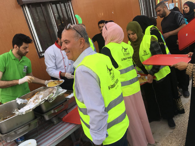 Teams and volunteers in Jordan help to serve meals to Syrian refugees at one of the daily iftaars